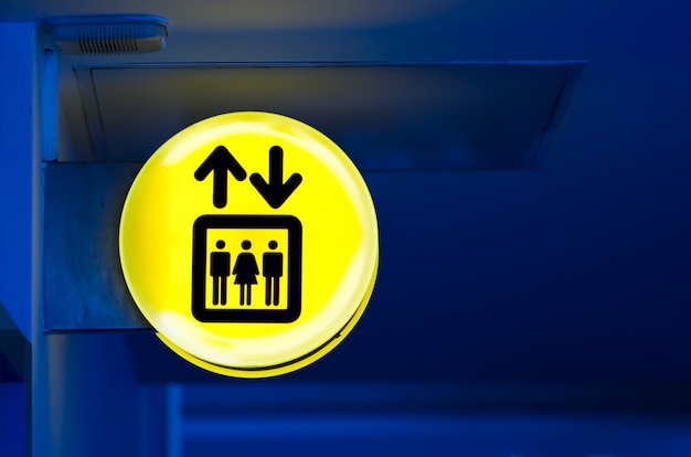 Ярко-желтый символ лифта или лифта, знак на синем фоне стены с неоновым светом. копировать пространство