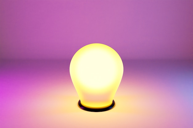 A bright yellow light bulb is lit on a pink isolated background. the light from the recess is shining brightly