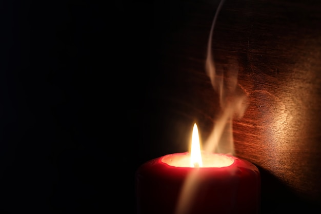 Bright yellow light of a burning candle flame in the dark