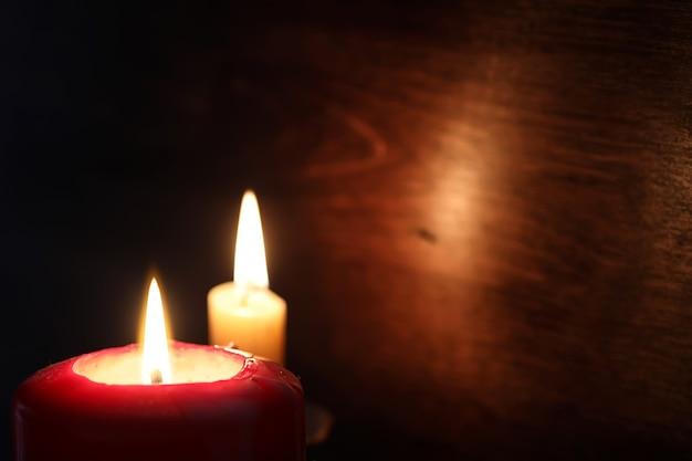 Ярко-желтый свет горящей свечи в темноте