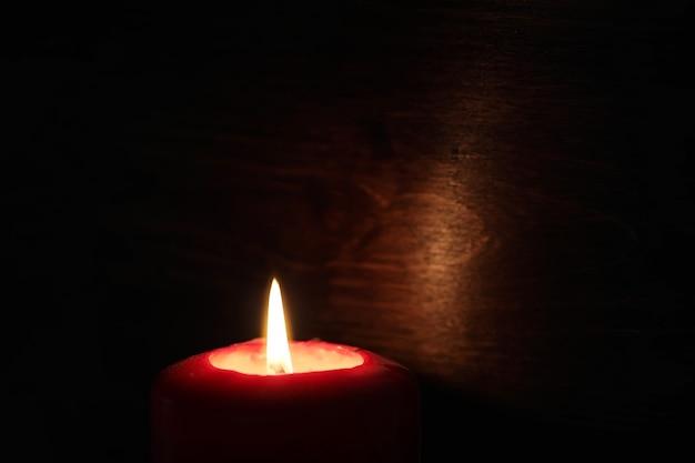 어둠 속에서 불타는 촛불 불꽃의 밝은 노란색 빛