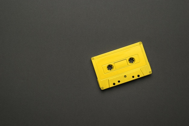 A bright yellow magnetic cassette on a black background. stylish retro equipment for listening to music. flat lay.