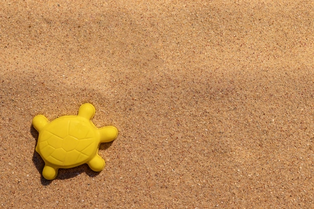 Bright yellow plastic children toy in shape of turtle on the sand. animal mold. concept of beach recreation for children. vacation with kids. top view. space for text.