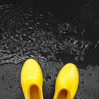 Bright yellow rubber boots stand in the rain on a black background covered with drops