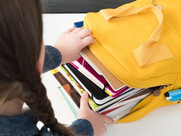 本でいっぱいの明るい黄色の学校のバックパック