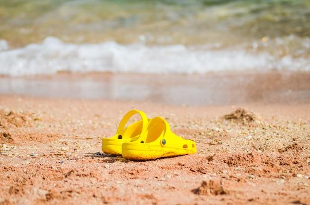 Bright yellow sneaker on a sandy seashore