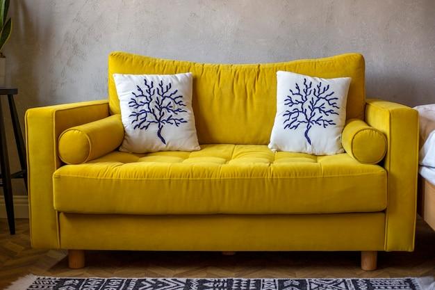 Ярко-желтый диван с белыми подушками у серой стены современный дизайн интерьера в стиле лофт