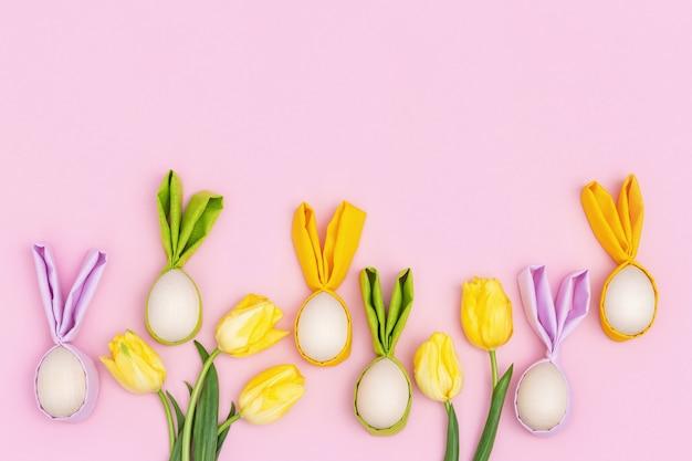明るい黄色の春の花のチューリップとイースターエッグ