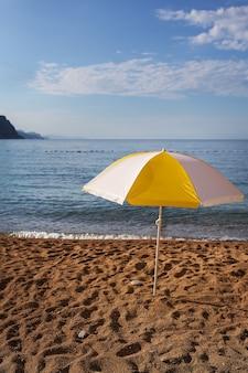 青い空を背景に明るい黄色の縞模様のビーチパラソル。ビーチでの休暇のコンセプト。碑文の場所。