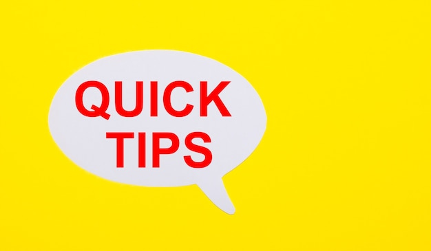 On a bright yellow surface, white paper with the words quick tips