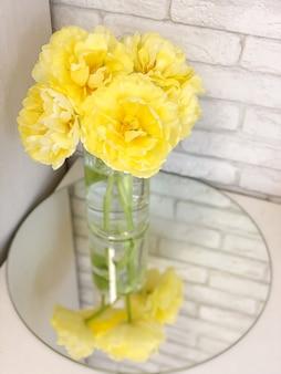 거울 근처 꽃병에 밝은 노란색 튤립. 큰 꽃 봉오리가있는 아름다운 봄 꽃