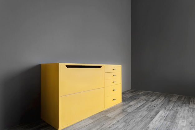 Bright yellow vintage chest of drawers in the room near a dark gray wall.