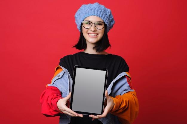 カラフルなベレー帽とジャケットの明るい若い女性は、赤のカメラで笑顔のモダンなタブレットを示しています