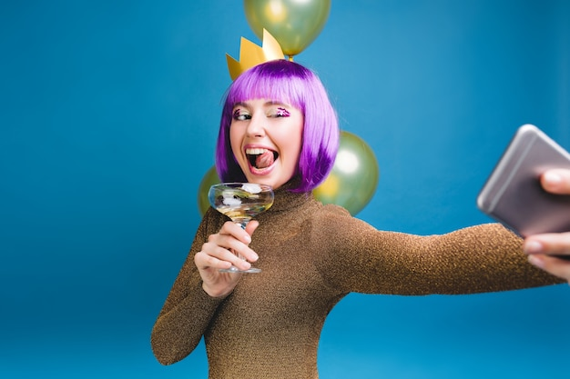 Brightful celebration emotions of young woman with purple haircut making selfie portrait . golden balloons, having fun, showing tongue, champagne, new year party, birthday  .