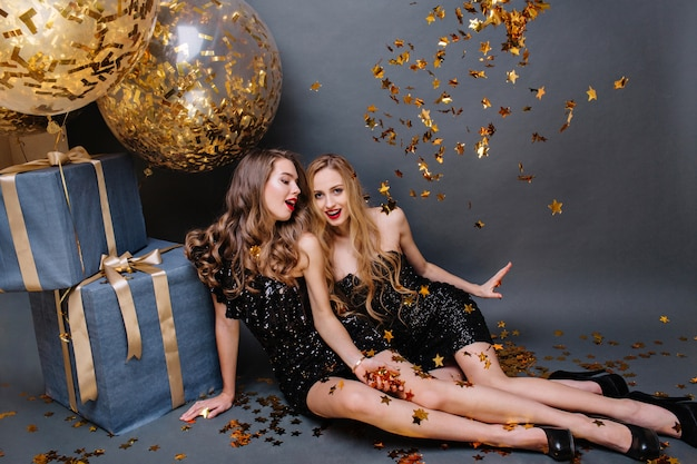 Brightful happy moments at celebrating party of two amazing young women in luxury black dresses chilling on floor. celebration, having fun, presents, golden tinsels, smiling.