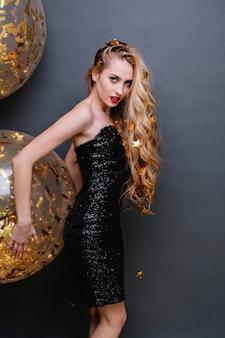 Brightful party time affascinante giovane donna in abito di lusso nero, capelli biondi ricci lunghi con orpelli dorati. grandi palloncini, tempo di festa, modello alla moda, umore allegro.