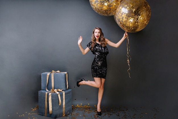 Brightful party time gorgeous young woman in black luxury dress, on heels, with long curly brunette hair holding big balloons full with golden tinsels. presents, birthday party.