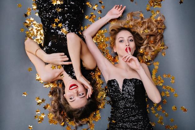 金色の見掛け倒しに横たわっている黒い高級ドレスを着た2人の楽しい魅力的な若い女性の上からの明るい肖像画。楽しんで、誕生日パーティー。