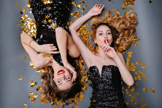 Brightful portrait from above two joyful attractive young women in black luxury dresses laying in golden tinsels. having fun, birthday party.