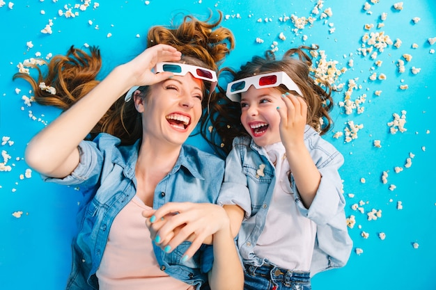 興奮した母と娘がポップコーンの青い床の上に敷設し、3 dメガネで笑って上から明るくスタイリッシュなイメージ。幸せな家族と過ごす時間、子供と一緒に楽しむお母さん、幸せを表現するエンターテイメント