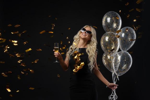 Яркие выражения счастливых эмоций удивительной блондинки, празднующей вечеринку. роскошные черные платья, улыбка, бокал шампанского, золотые мишуры, воздушные шары, длинные вьющиеся волосы.
