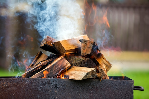 Brightly burning in metal box firewood for barbecue outdoor