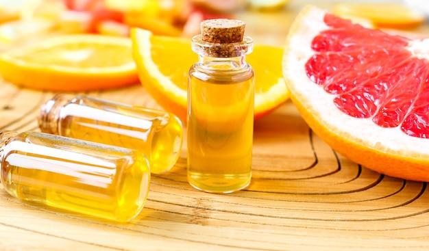 木製の背景に鮮やかな色の柑橘類のスライスとアロマセラピーオイルのボトル