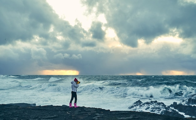 Brightly dressed young woman tourist makes a photo of a beautiful seascape, standing on the shore with black volcanic sand in cloudy weather.