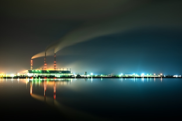 Brightly illuminated coal power plant high pipes with black smoke moving upwards polluting atmosphere at night with reflections of it in lake water.