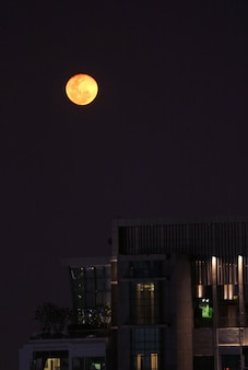 Brightly orange color full moon over the city of bangkok, thailand