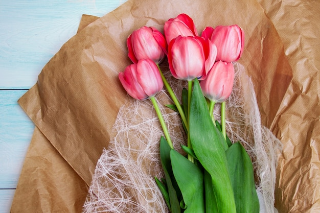 Brightly pink tulips lie on craft paper on a blue wooden background. flat lay, top view