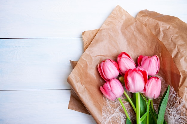 Brightly pink tulips lie on kraft paper on a light blue wooden background. flat lay, top view