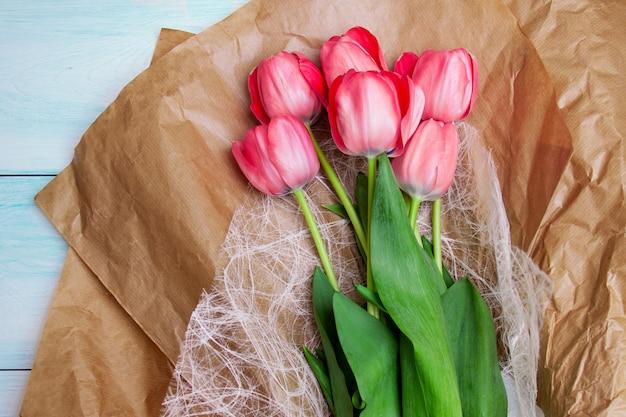Ярко-розовые тюльпаны лежат на крафтовой бумаге на синем деревянном фоне. плоская планировка, вид сверху