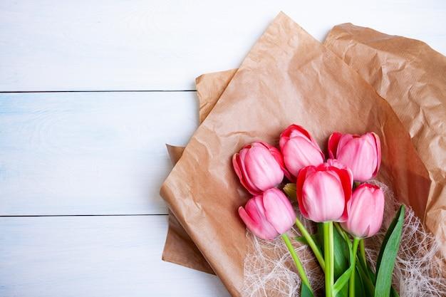 Ярко-розовые тюльпаны лежат на крафт-бумаге на голубом деревянном фоне. плоская планировка, вид сверху