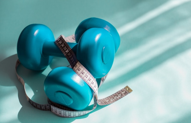 Brightly turquoise dumbbells, a tape measure on a blue background in the sun. healthy life
