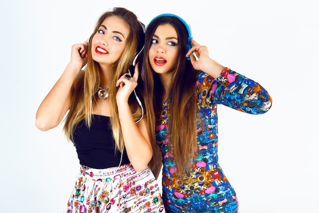 Brigit fashion portrait of two best friends dj girls, wearing dresses, headphones and listening their favorite music.