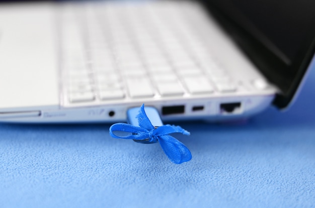 A brilliant blue usb flash drive with a blue bow is connected to a white laptop