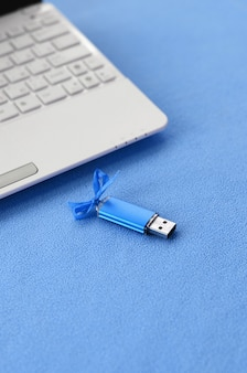 Brilliant blue usb flash memory card with a blue bow lies on a blanket of soft