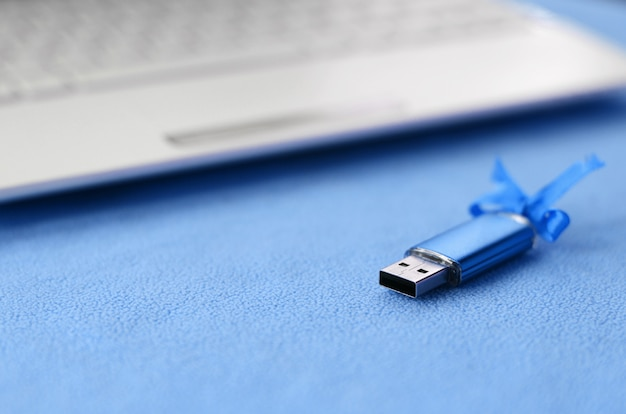 Brilliant blue usb flash memory card with a blue bow lies on a blanket