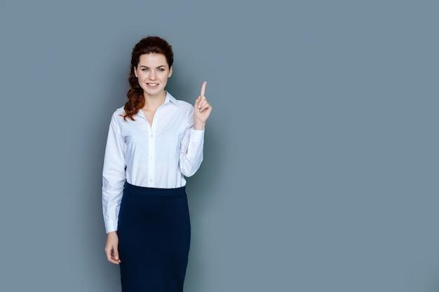 훌륭한 아이디어. 기발한 생각을하면서 웃고 그녀의 손가락으로 가리키는 기쁘게 좋은 똑똑한 여자