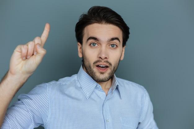 Великолепная идея. умный приятный молодой человек показывает пальцем вверх и смотрит на вас, имея гениальную идею
