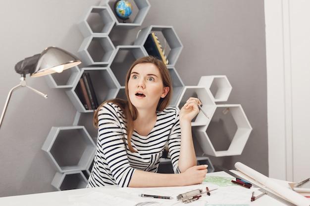 素晴らしいアイデア。縞模様のシャツを着た黒髪の若い見栄えの良い面白いヨーロッパの女性建築家は、プロジェクトの問題の良い解決策が頭に浮かんだとき、オフィスでチームプロジェクトに取り組みました。