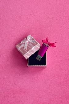 Brilliant pink usb flash memory card with a pink bow lies in a small gift box