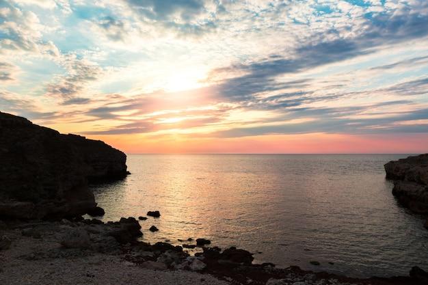 Великолепное место для отдыха на пляже на рассвете и фоне морских скал