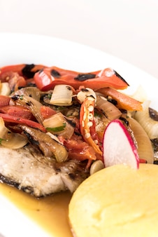 Brine fish plate with vegetables, chili and polenta, placed on white plate