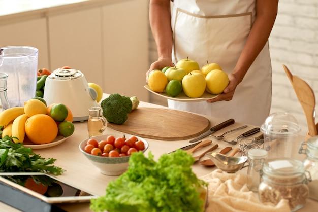 テーブルに果物をもたらす