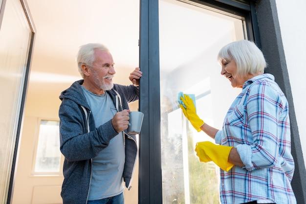 お茶を持参してください。愛するひげを生やした青い目の夫は、妻がドアを掃除しているお茶を持ってきている間、素晴らしい気分になります