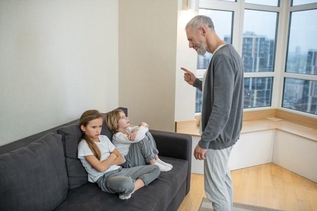 プロセスを立ち上げます。白髪のひげを生やした男が子供たちと話し、不満を感じている