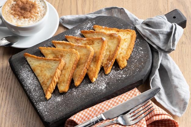 木製のまな板に粉砂糖を添えたブリオッシュフレンチトースト