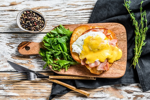 Brioche sandwich with bacon, egg benedict and hollandaise sauce